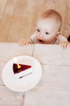 Happy birthday to me! top view of cute little baby looking at the plate with cake on it and keeping mouth open