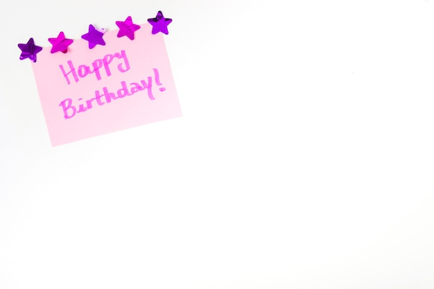 Happy birthday message on pink paper decorated with star shape on white background