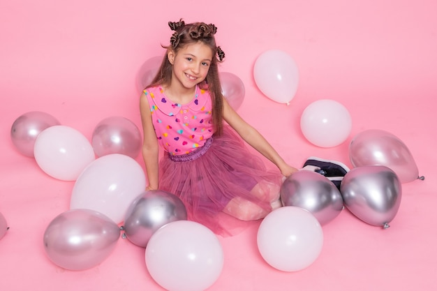 생일 축하해요 핑크 드레스를 입은 어린 소녀. 촛불과 장미와 흰색 케이크입니다. 흰 벽에 파티를 위한 흰색과 분홍색 풍선과 색종이 조각이 있는 생일 장식. 생일 축하해.