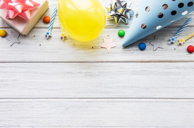 С днем рождения или партии фон. плоский лежал с днем рождения шляпы, конфетти и ленты на белом деревянном фоне. вид сверху. скопируйте пространство.