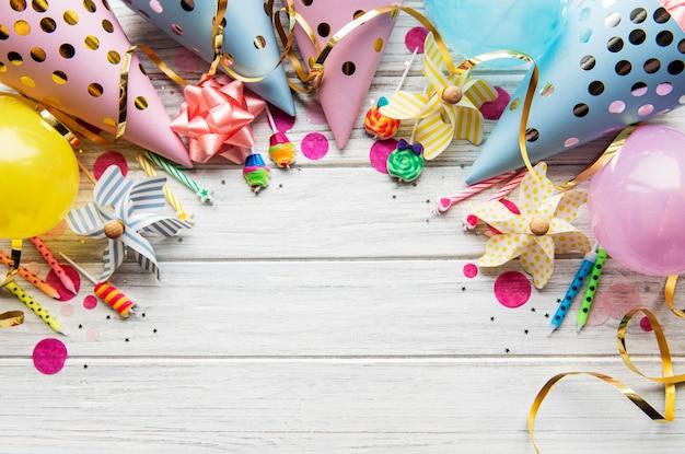 お誕生日おめでとうまたはパーティーの背景。白い木製の背景に誕生日の帽子、紙吹雪、リボンでフラットレイ。上面図。スペースをコピーします。