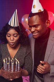 お誕生日おめでとうパーティーの女の子がろうそくを吹く