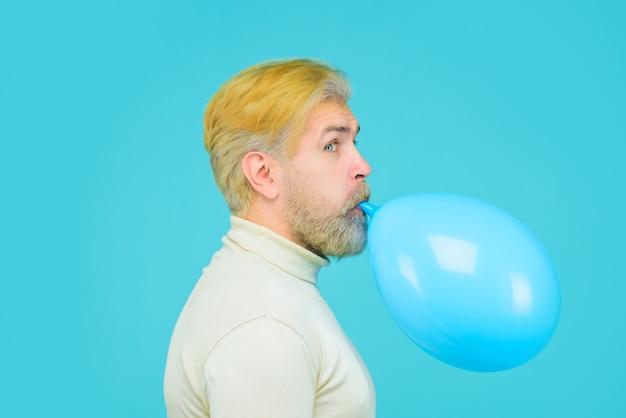 파티에 생일 축하 준비를 하는 매력적인 남자가 파란 풍선을 불고 있습니다 세련된 남자가 부풀립니다