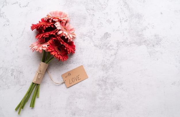 誕生日おめでとう。赤いガーベラのデイジーの花とコンクリートのテーブルに愛の言葉でクラフトラベルタグ、フラットレイ