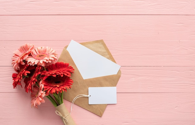 Happy birthday. red gerbera daisy flowers, envelope and blank label tag on pink wooden table