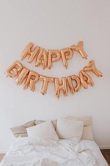 Happy birthday! rose gold sparkling balloons on white