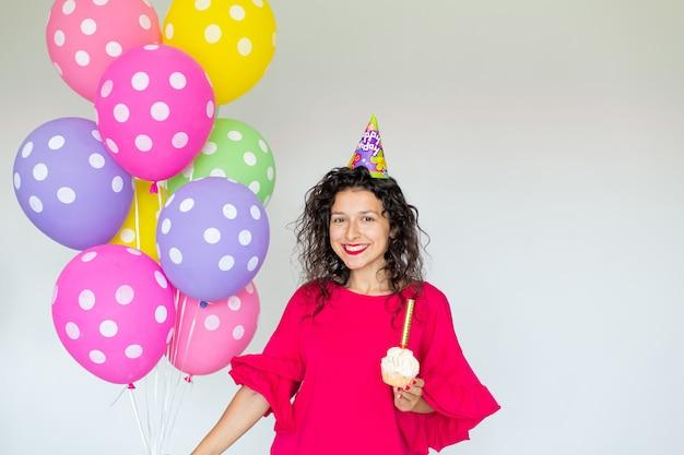 С днем рожденья. сексуальная брюнетка девушка позирует с воздушными шарами, фейерверками, красочными воздушными шарами и праздничным тортом на белом фоне.