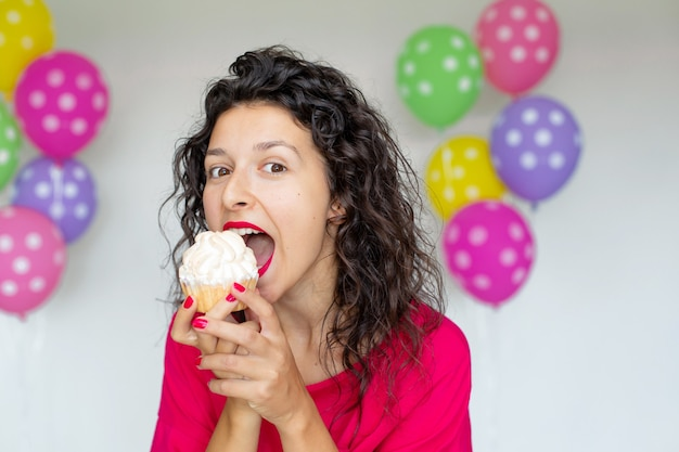 С днем рождения. сексуальная брюнетка девушка позирует с воздушными шарами, фейерверками, красочными воздушными шарами и праздничным тортом на белом фоне.