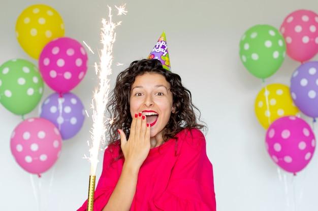С днем рождения. сексуальная брюнетка девушка позирует с воздушными шарами, фейерверками, красочными воздушными шарами и праздничным тортом на белом фоне