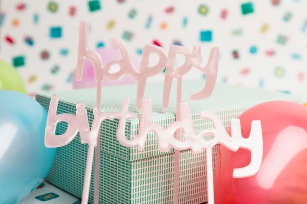 プレゼントボックスと風船の近くの幸せな誕生日サイン