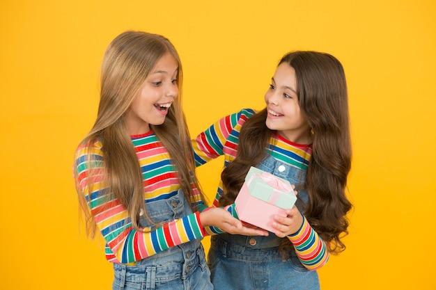 생일 축하해. 작은 아이는 생일 소녀에게 선물 상자를 줍니다. 생일 선물. 어린 아이들은 생일을 축하합니다. 가족. 우정. 휴일 쇼핑.