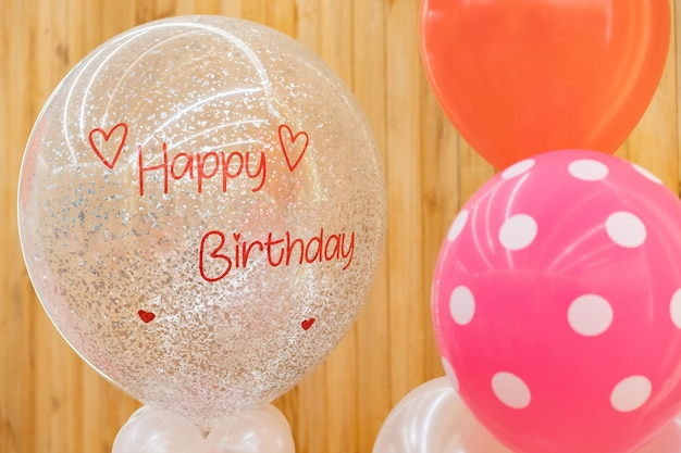 A happy birthday text on the balloon for gift in the birthday party standing in front of wood background.