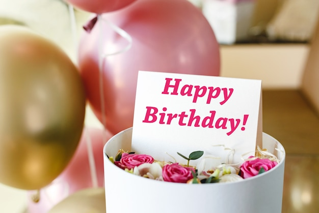 Happy birthday text on gift card in flower box near festive pink and gold balloons. beautiful bouquet of fresh flowers roses in box with greeting card happy birthday. Premium Photo