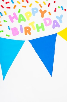 Happy birthday text with candies and bunting on white background