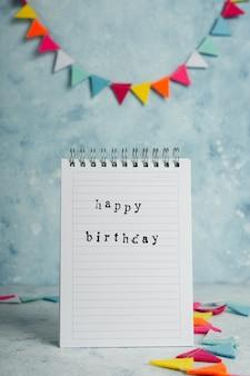 Auguri di buon compleanno su notebook con ghirlanda