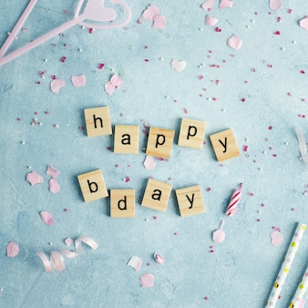 Happy birthday wish in wooden letters with candles and straws