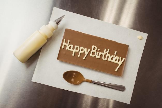 С днем рождения написано на шоколадной табличке