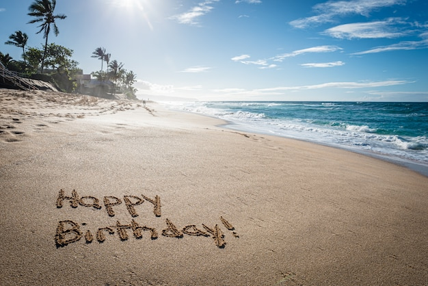 Happy birthday written in the sand on sunset beach in hawaii with palm trees and the ocean