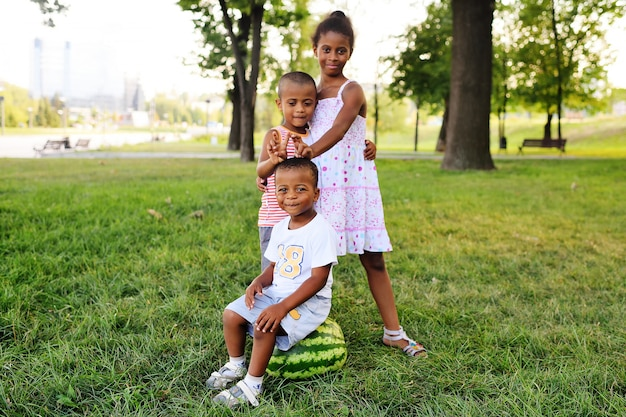 Happy black african american kids playing with a big watermelon in the park on the grass and smiling.