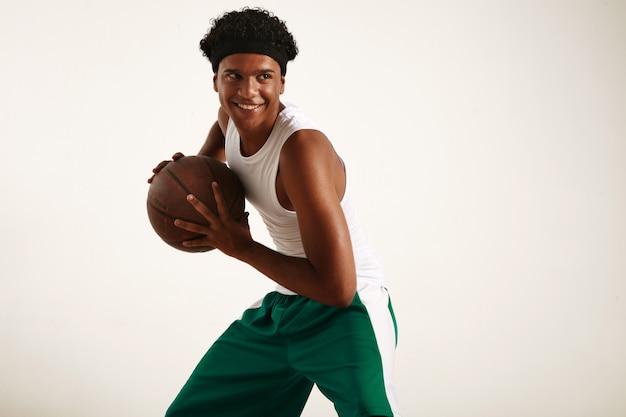 Счастливый черный баскетболист в зелено-белом костюме держит винтажный коричневый баскетбольный мяч, динамичная поза на белом