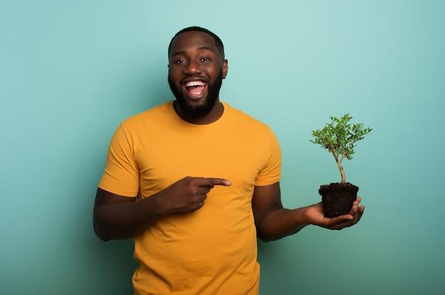 幸せな黒人の少年は、植える準備ができている小さな木を示しています