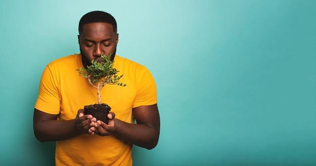 幸せな黒人の少年は、植えられる準備ができている小さな木にキスします