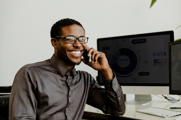 Счастливый черный бизнесмен разговаривает по телефону