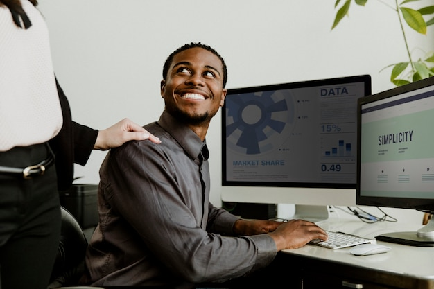 Happy black businessman working on a computer screen mockup