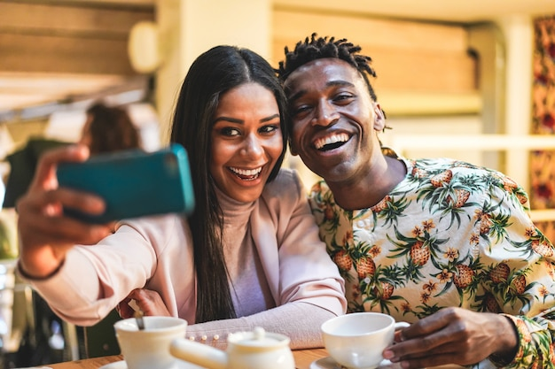 Happy black couple drinking coffee inside bakery while taking selfie with mobile phone
