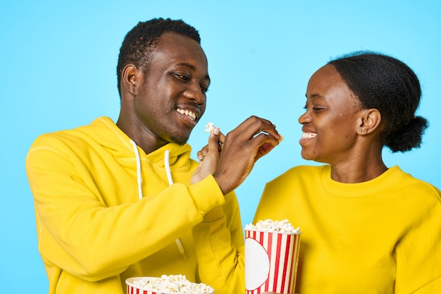 Happy black couple eating pop-corns and watching movie