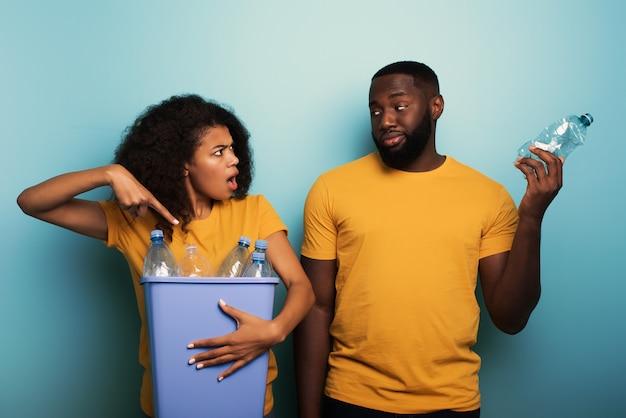 행복한 흑인 부부는 밝은 파란색 위에 병이 든 플라스틱 용기를 잡고