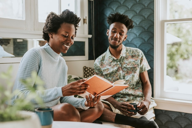 Happy black couple reading a book at home