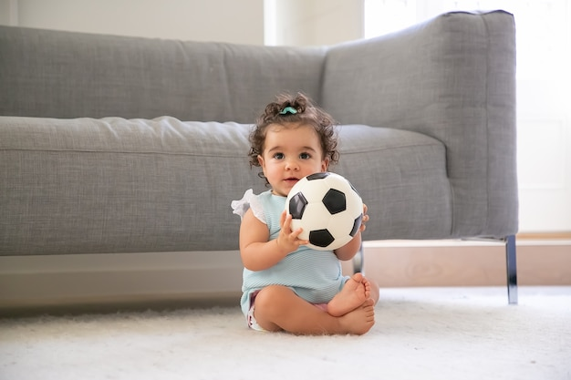 Happy black curly haired baby girl in pale blue clothes sitting on floor at home, looking away, playing soccer ball. front view. kid at home and childhood concept
