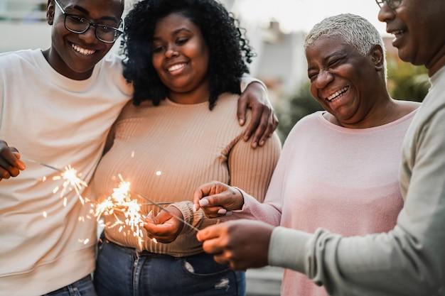 Счастливая черная семья празднует с бенгальскими огнями на открытом воздухе дома - фокус на лице матери