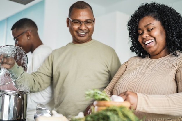 自宅のキッチンで料理をする幸せな黒人家族-娘の顔に焦点を当てる