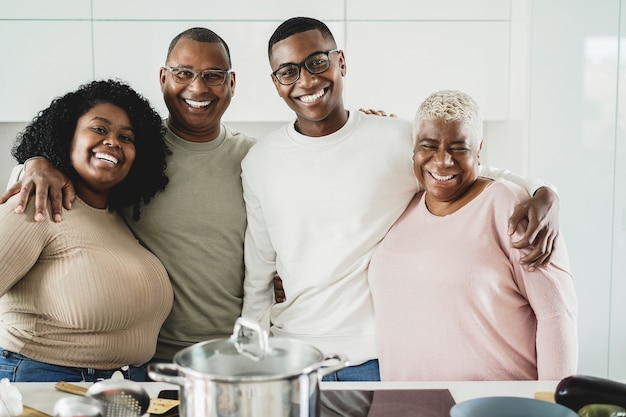 Happy black family cooking inside kitchen at home - main focus on father face