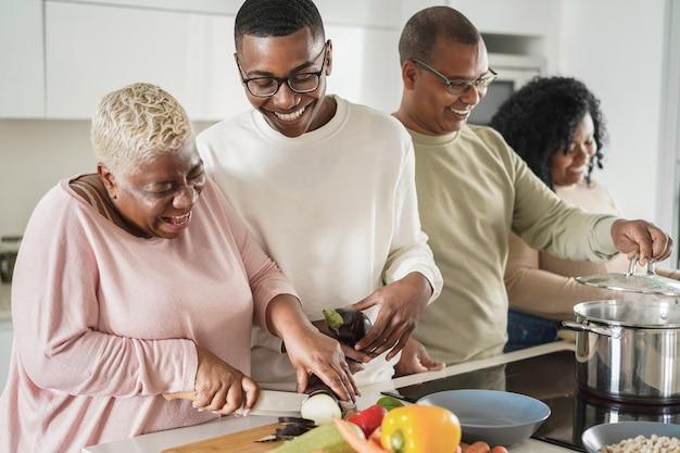 Счастливая черная семья, готовящая веганскую еду на кухне дома - сосредоточьтесь на лице сына