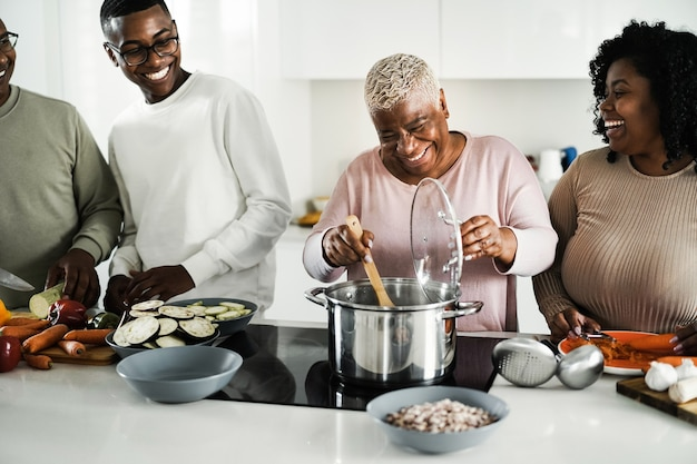 집에서 부엌 안에 채식주의 음식을 요리하는 행복 한 흑인 가족