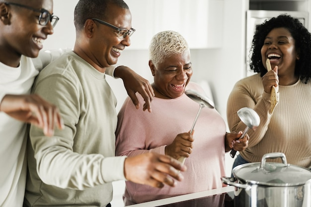 집에서 부엌에서 채식주의 자 음식을 요리하는 동안 행복한 흑인 가족 춤