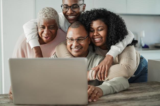 Счастливая черная семья делает видеозвонок дома - основное внимание уделяется лицу отца