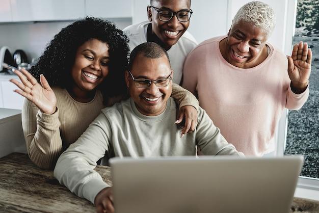 Счастливая черная семья делает видеозвонок в помещении дома - основное внимание уделяется правому лицу девушки