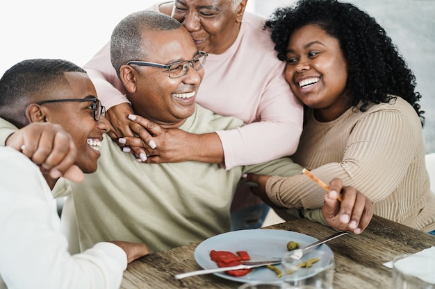 Happy black family eating lunch at home - father, daughter, son and mother having fun together sitting at dinner table - main focus on man face