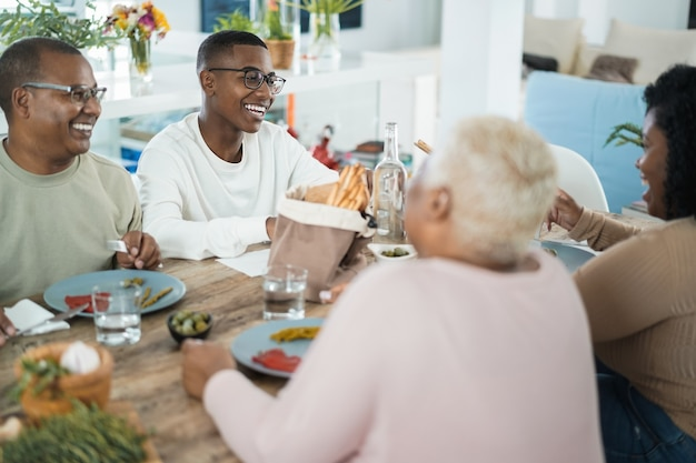 Happy black family eating lunch at home - father, daughter, son and mother having fun together sitting at dinner table - main focus on son face