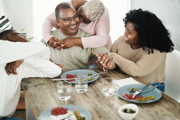 Happy black family eating lunch at home - main focus on father face