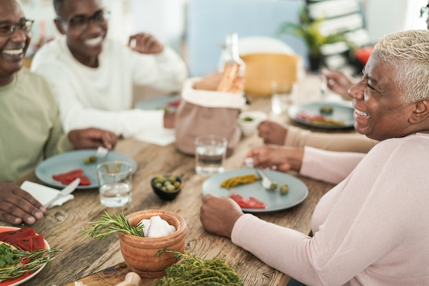Happy black family eating lunch at home - main focus on mum face
