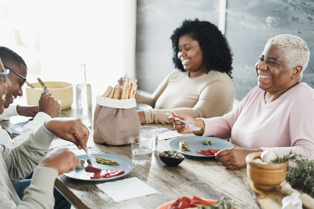 Happy black family eating lunch at home