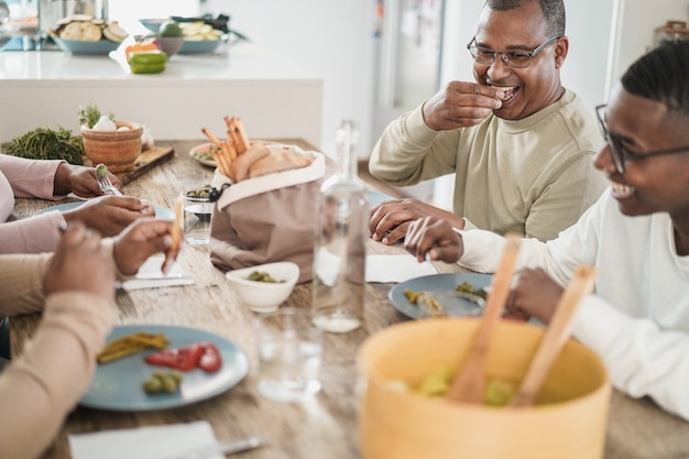 Happy black family eating lunch sitting at dinner table at home - focus on fathers face