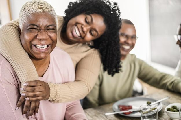 Счастливая черная семья вместе обедает дома - основное внимание уделяется лицу матери