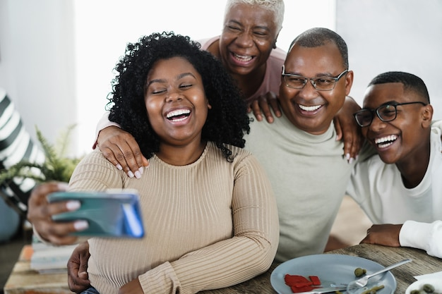 Happy black family taking a selfie while eating lunch at home - focus on girl face