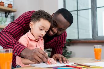 幸せな黒人の父と息子のテーブルで描く